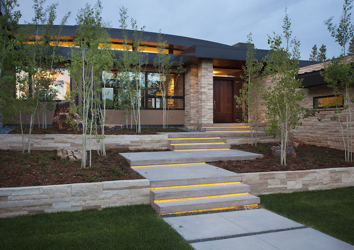lights on the stairway, patches of grass, small trees, pool landscaping ideas, stone borders