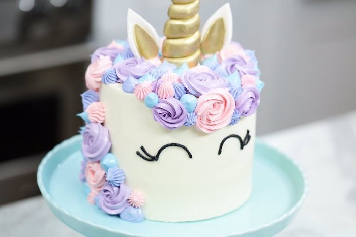 blue cake stand, unicorn cake pictures, pink purple and blue roses on white fondant, gold horn and ears
