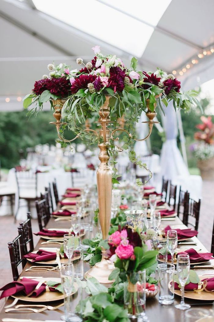 pink and red flower bouquets in a candelabrum, red napkins on the table, wedding ceremony decorations