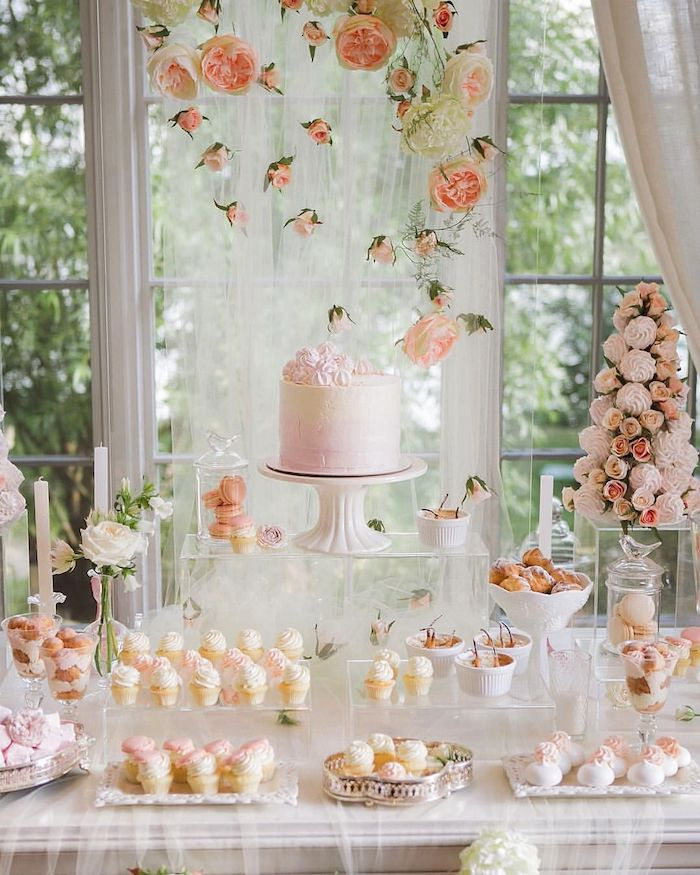 cake on a cake stand, cupcakes on trays, hanging roses from the ceiling, wedding table decorations