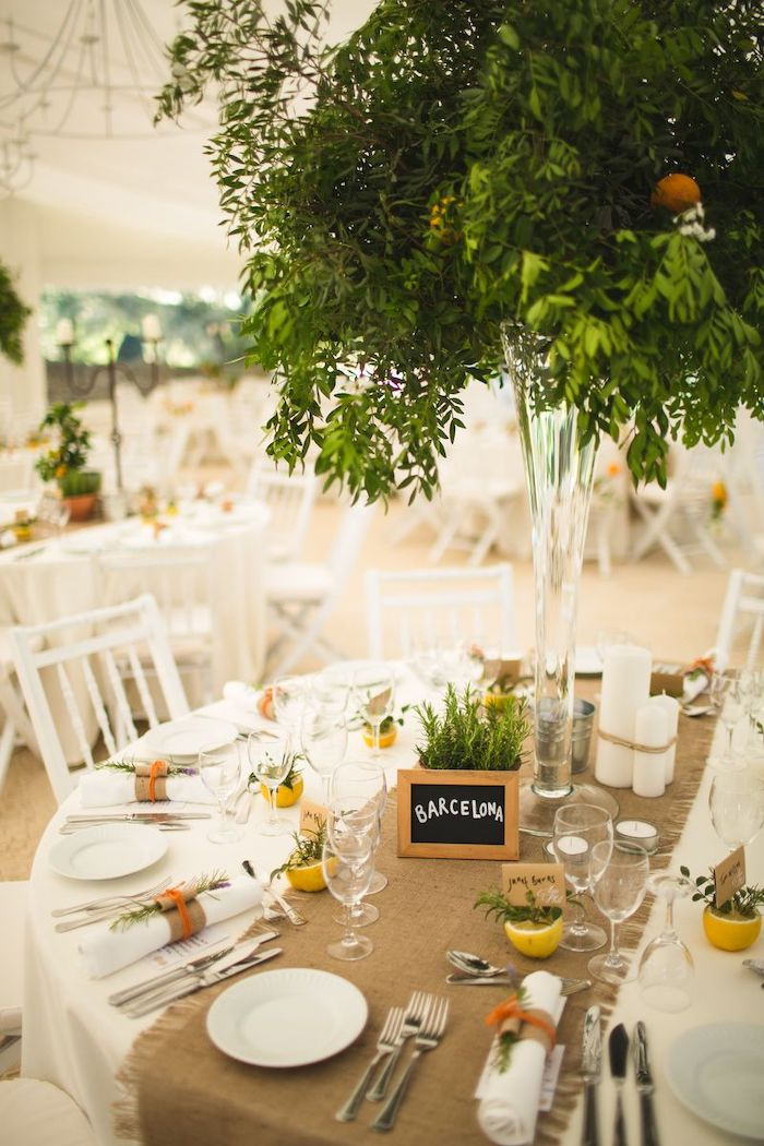 green leaves flower arrangements in a high vase, wooden barcelona sign on the table, wedding ceremony decorations