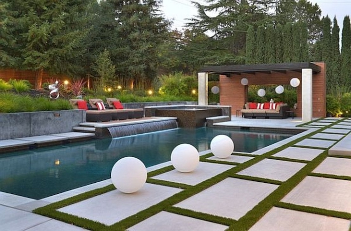 small patches of grass between the tiles, large pool, grass patch with bushes, pool landscaping ideas, tall trees