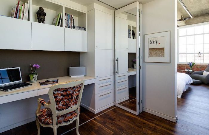 white cabinets and bookshelves, printed vintage chair, small home office desk, dark wooden floors