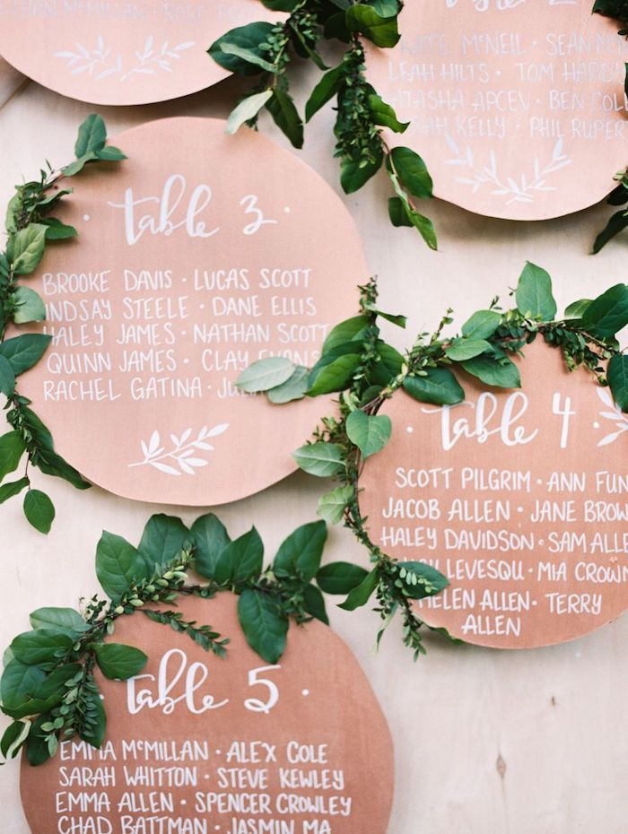 copper round seating chart with green leaves, wedding table decoration ideas
