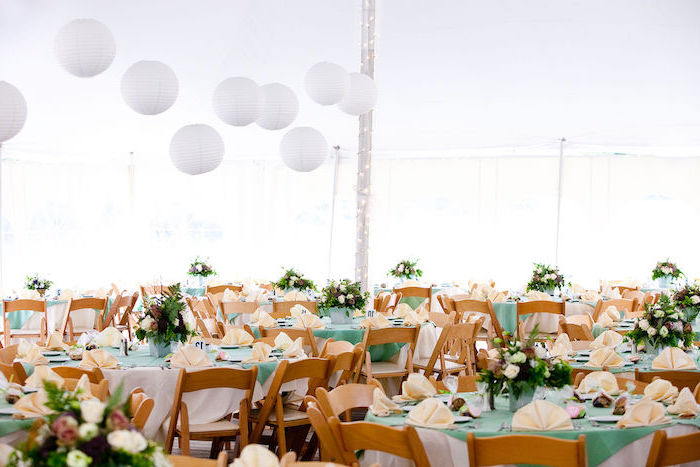hanging lanterns, white and pink roses flower arrangements on the tables, orange napkins, wedding decor