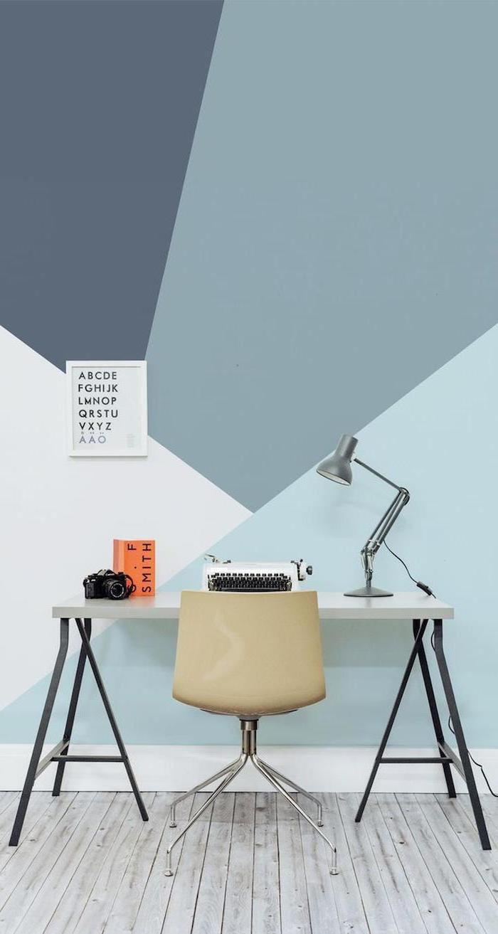 wooden desk, beige plastic chair, small home office desk, shades of blue geometrical wall, metal desk lamp