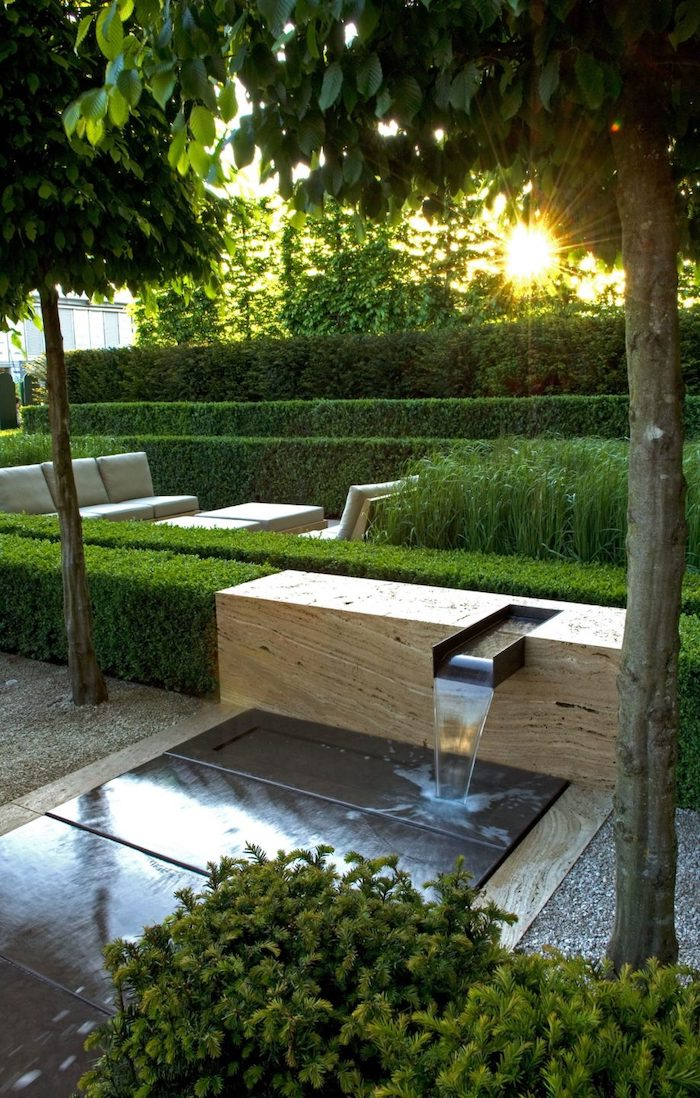 levelled hedges, small water fountain, patches of grass, backyard landscaping ideas, tall trees