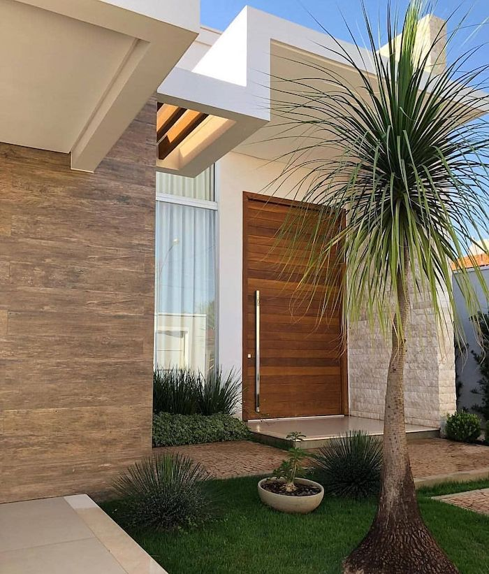 small grass patch with bushes, front yard landscaping ideas with rocks, small palm tree, ceramic pot with a plant