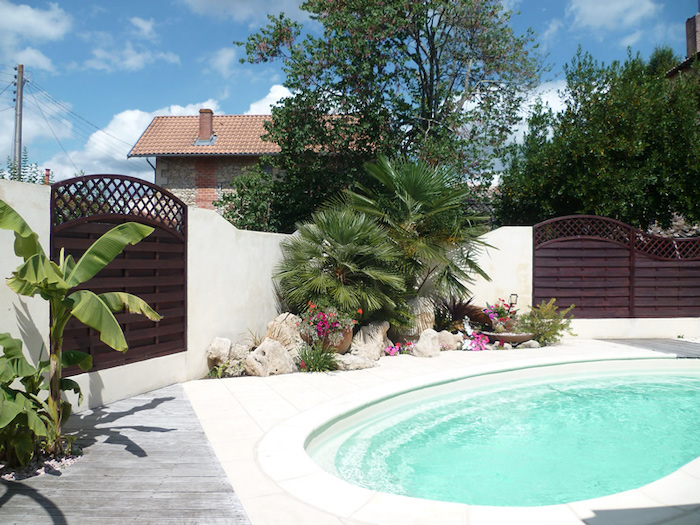 small pool, small palm trees, front yard landscaping ideas with rocks, flower beds with rocks, ceramic pots