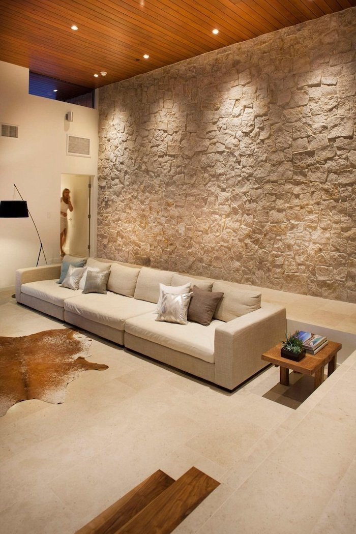 stone wall, large white sofa, small wooden side table, wooden ceiling, feature wall