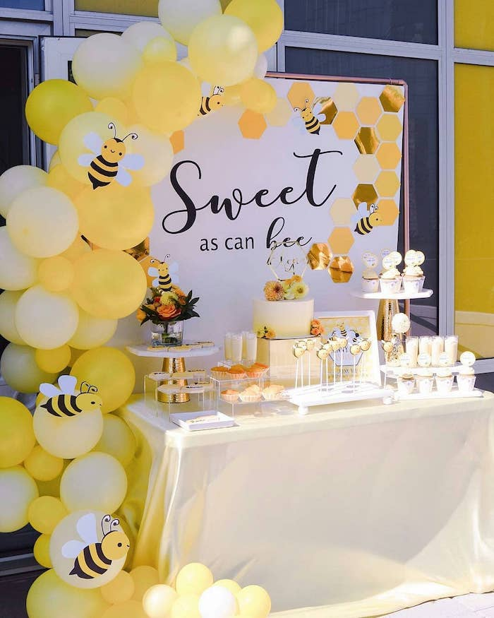 sweet as can bee banner, yellow balloons, paper bees, unique boy baby shower themes, cake and sweets on the table