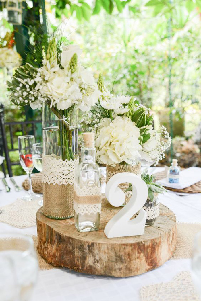 wooden centrepiece with a table number, white flower bouquets in vases, diy wedding decorations