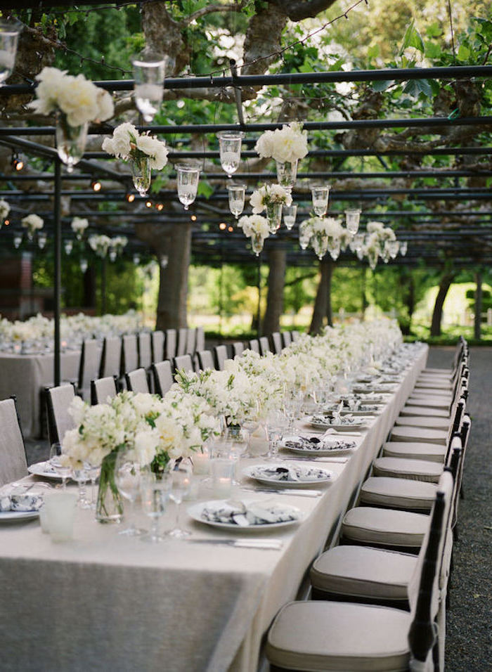 candles and white flower bouquets hanging from the ceiling, white bouquets on the table, wedding ideas for spring