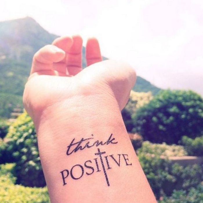 think positive inscription, chest tattoos for females, tattoo on the wrist, mountain in the background