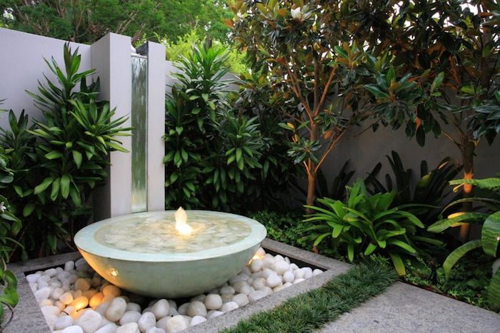 small ceramic water fountain, patch of white rocks, patches of bushes and small trees, landscape border ideas