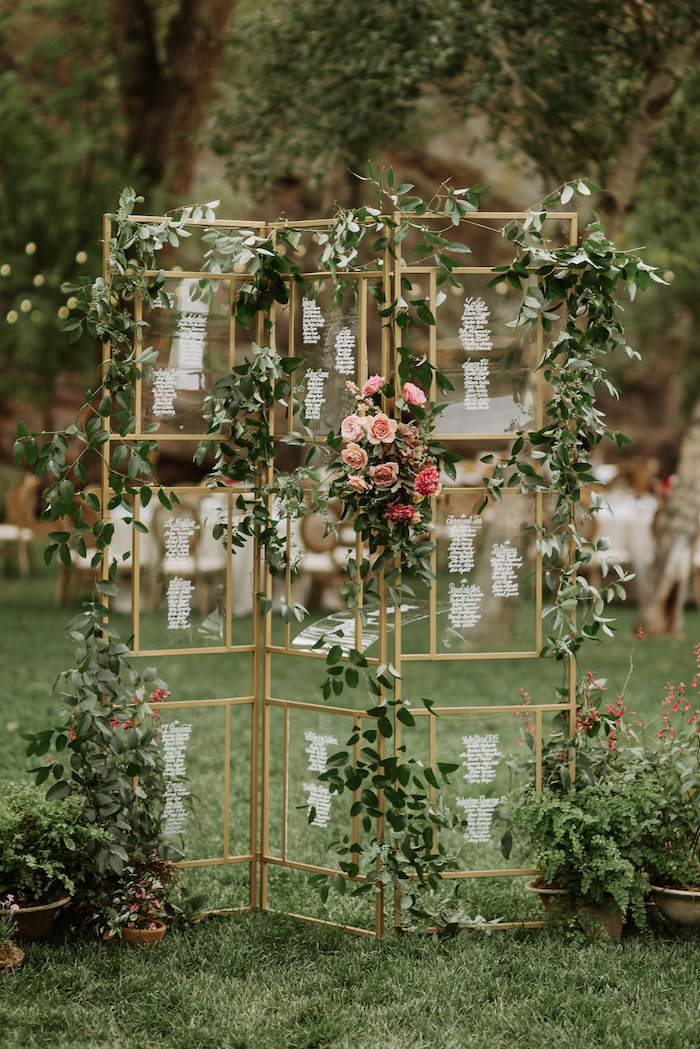glass geometrical seating chart, hanging roses and leaves, trees in the background, wedding table decoration ideas