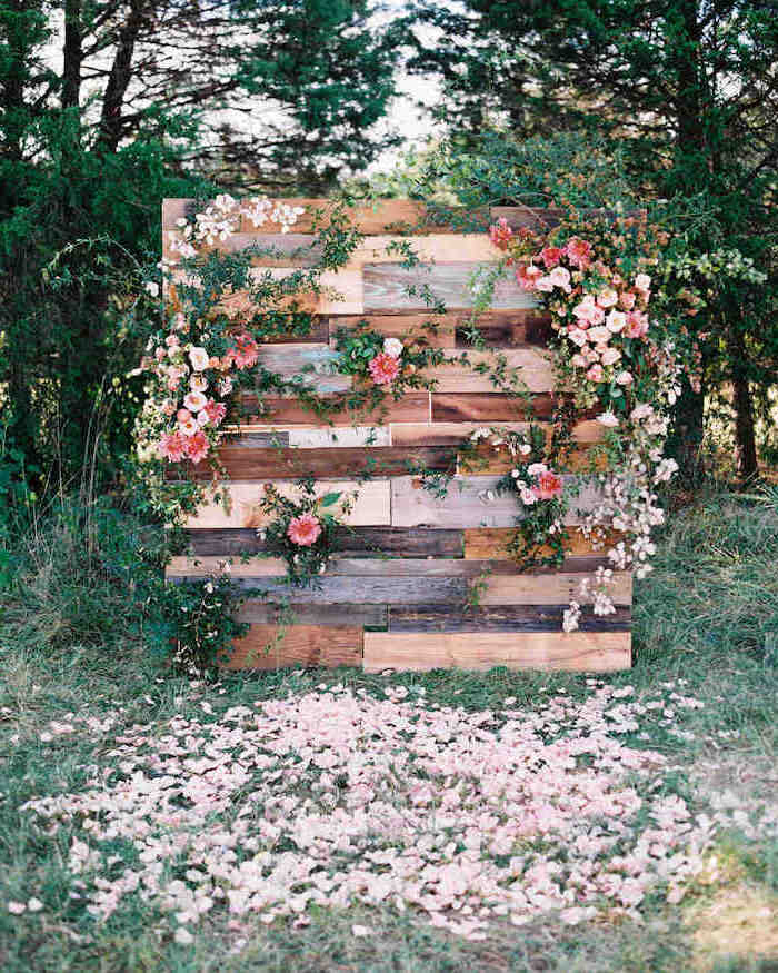 wooden backdrop with pink and white flowers hanging, rose petals in the grass, trees in the background, rustic wedding ideas