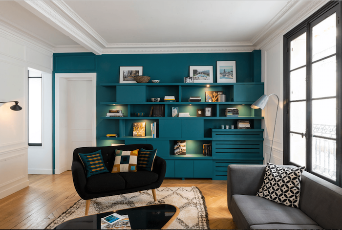 black velvet sofa, grey sofa, turquoise wall with bookshelves and cabinets, wallpaper accent wall