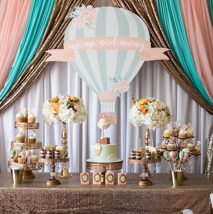 up and away air balloon, pink blue and white tulle, cake and sweets on the table, baby shower themes for boys
