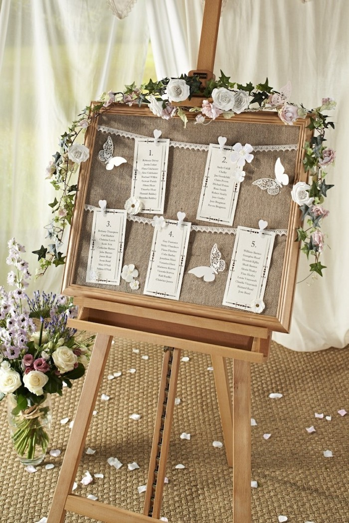 wooden stand with hanging white roses, paper pinned with pins on a white string, rose petals on the floor, wedding reception decoration ideas