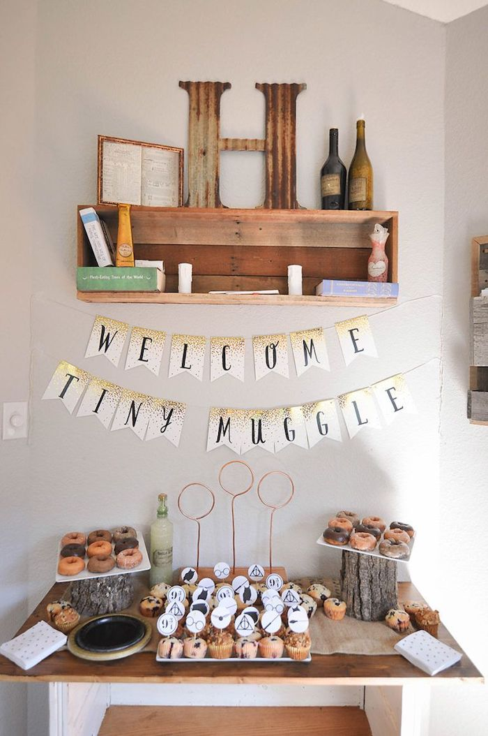 welcome tiny muggle banner, cupcakes and donuts on the table, baby shower ideas for boys