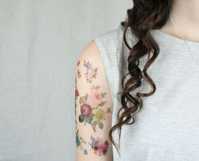 flower bouquets on shoulder, brown curly hair, small tattoo ideas for men, grey top, white background