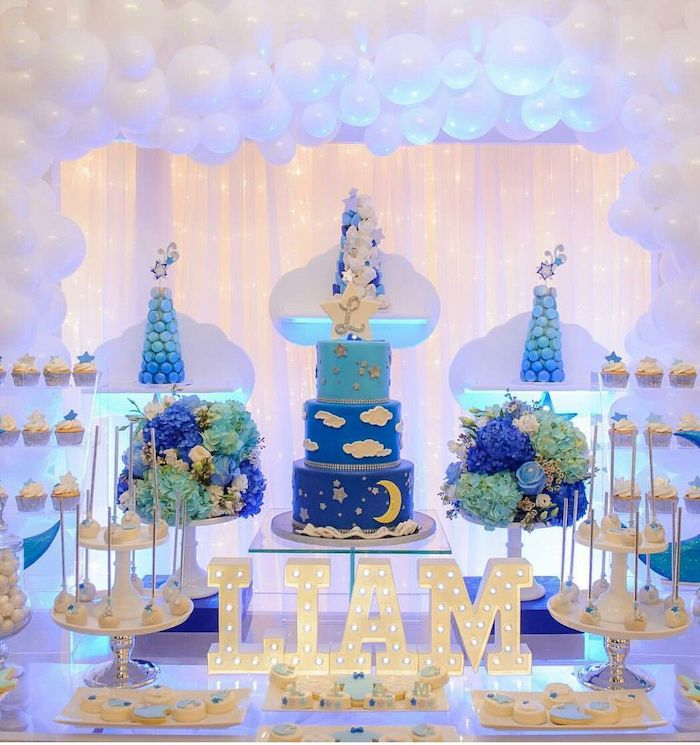 white balloon arch, cake and sweets on the table, baby boy baby shower themes, liam lights on the table