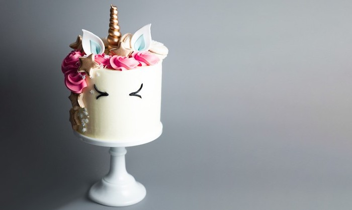 white cake stand, grey background, unicorn cake, white frosting covered with pink roses and sprinkles