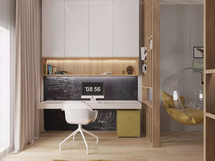 chalk wall, white cabinets and desk, wooden bookshelf, small home office desk, white mesh chair, green drawers