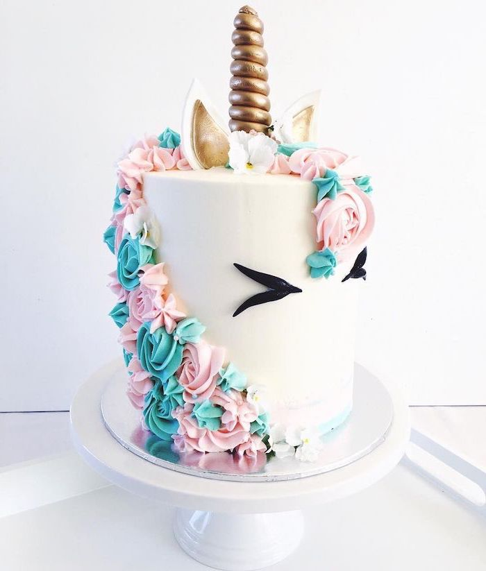 pink and blue roses on white fondant, gold horn and ears, white cake stand, easy unicorn cake