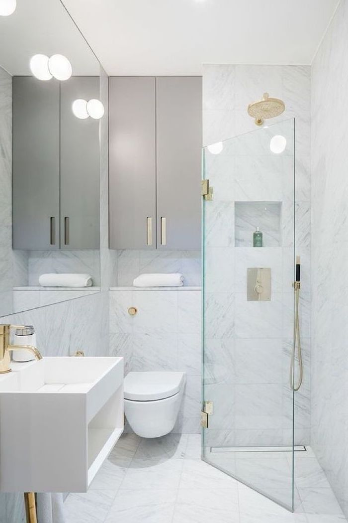small bathroom decorating ideas, white tiled walls and floor, glass shower door, grey cabinets, floating sink