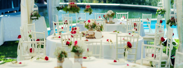 hanging bird cages with flowers, red roses in vases on the tables, white and red roses flower bouquets, hanging decorations