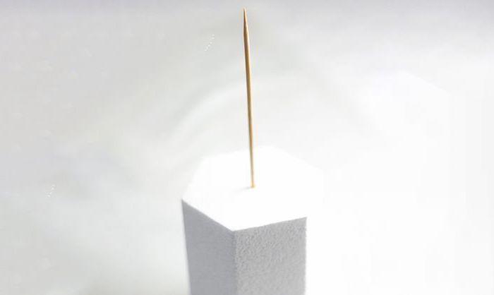 white background, unicorn birthday cake, wooden skewer in white styrofoam
