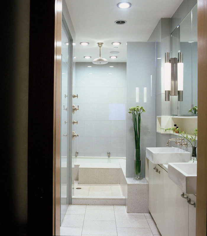 white and blue tiled walls and floor, white cabinets, bathroom wall ideas, flowers in a vase