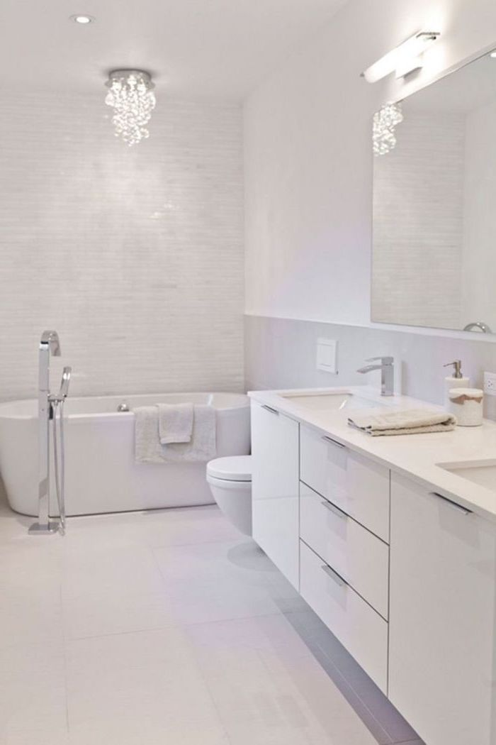 white tiled floor and walls, white floating cabinets, bathroom wall ideas, hanging chandelier