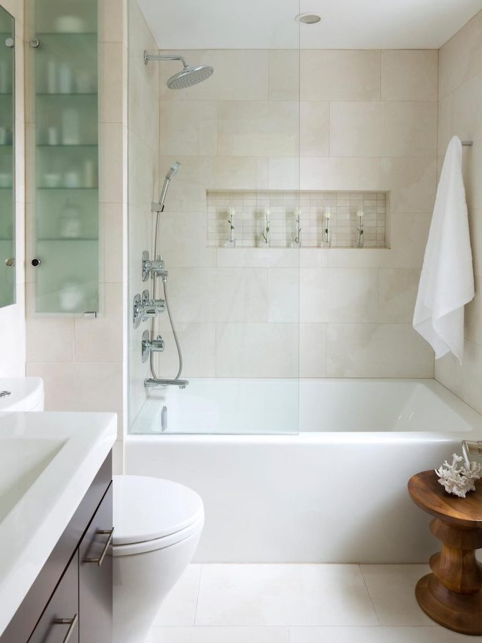 white tiled walls and floor, wooden stool and cabinets, modern bathroom design, glass shower door