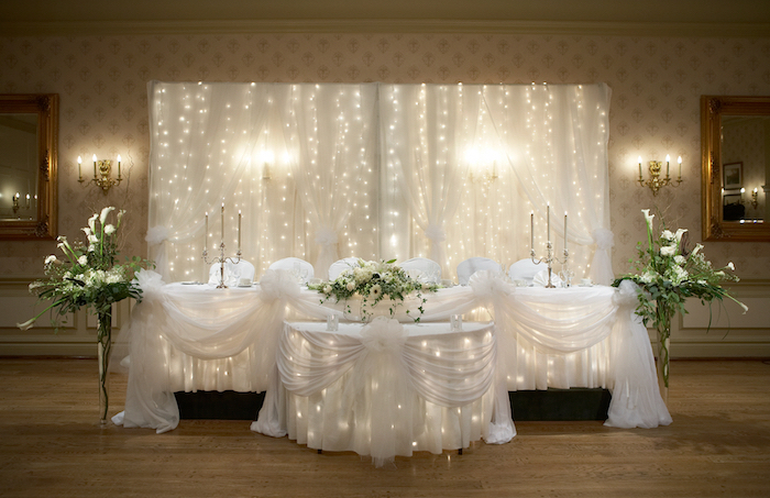 white tulle with fairy lights backdrop, white and green flower arrangements, candelabrum with candles, rustic wedding centrepieces