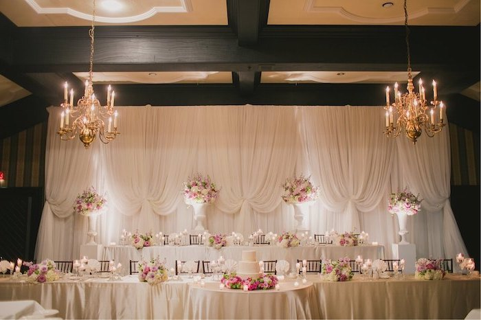 white tulle backdrop, candelabrum chandeliers with candles, pink and white flower bouquets in large vases, rustic wedding centrepieces