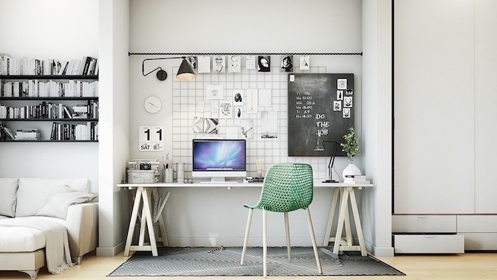 wooden desk, green mesh chair, chalk board, office pictures, black bookshelves, dark grey rug