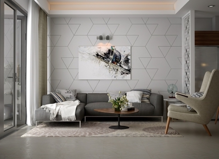 white geometrical wallpaper, dark grey corner sofa, painting accent walls, large white armchair