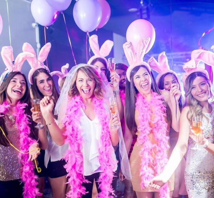 bunny ears on ladies, bachelorette party ideas, hot pink garlands, ladies having fun