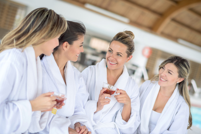 ladies in white robes, drinking tea, bachelorette party ideas, women smiling