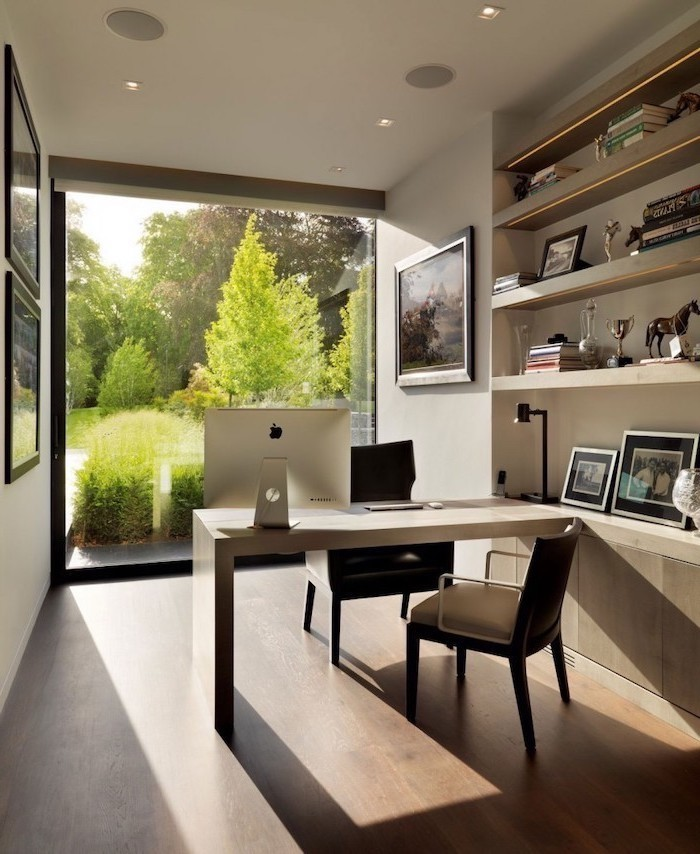 wooden desk and bookshelves, work office decorating ideas, two black chairs, framed photos