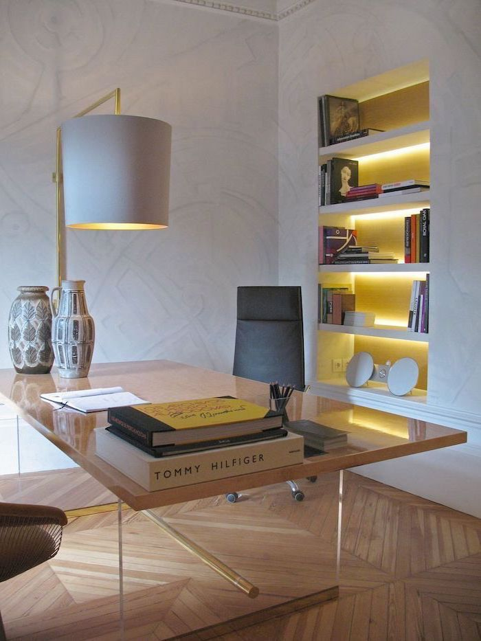 metal desk, white bookshelves and desk lamp, black leather chair, living room desk, wooden floor