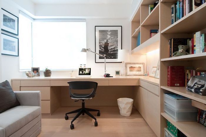 wooden bookcase with shelves and cabinets, work office decor, grey sofa, black chair, white walls with framed photos