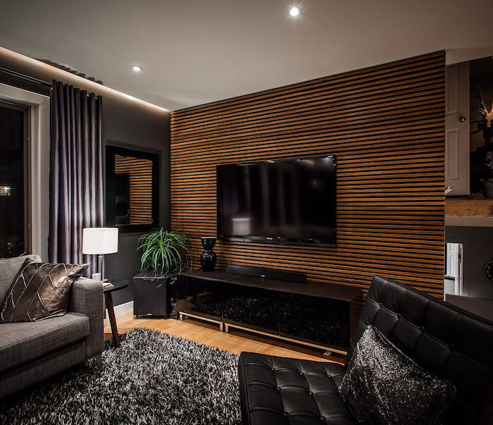 black leather sofa, painting accent walls, wooden striped wall, black rug, grey sofa