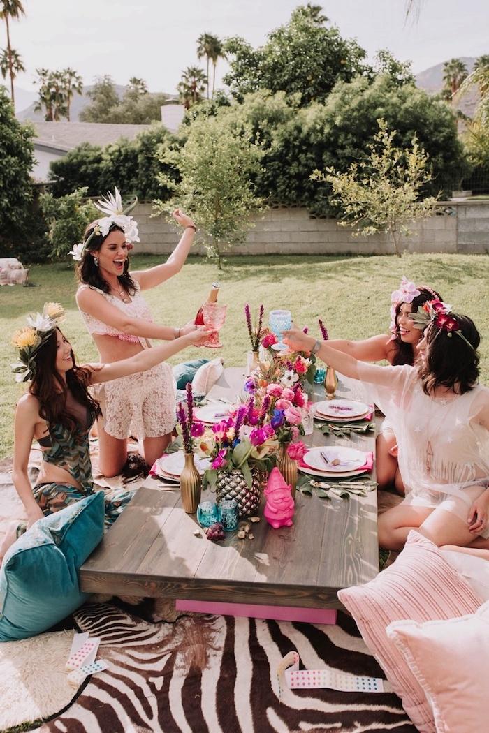 women smiling, women sitting in a garden, flower arrangements on the table, bachelorette party ideas, flower crowns