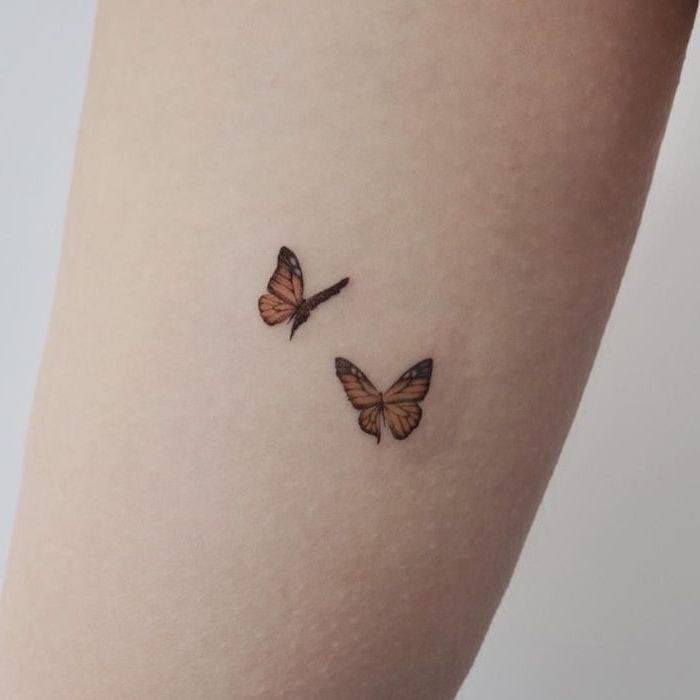 two yellow butterflies, back tattoos for girls, tattoo on the forearm, white background