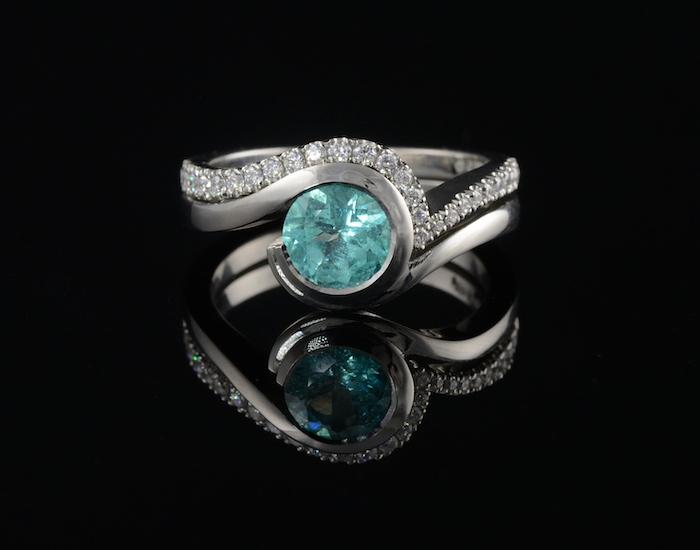 round aquamarine stone, black background, gold engagement rings, diamond studded band