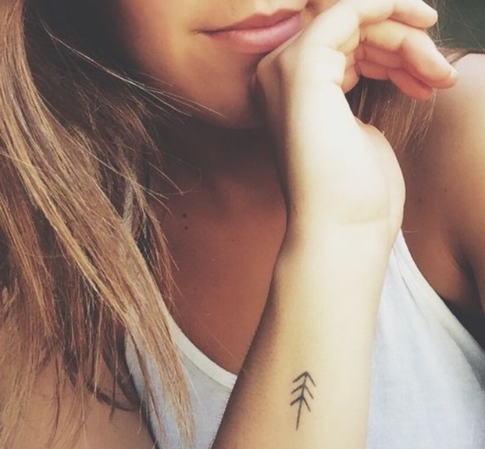 arrow forearm tattoo, small tattoo ideas, woman wearing a white top, with long blonde hair